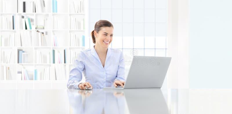 微笑的妇女在有计算机的办公室在书桌 免版税图库摄影