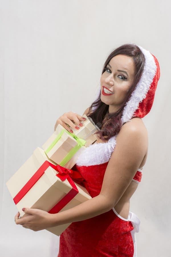 微笑的妇女在有许多礼物盒的圣诞老人服装 免版税库存照片