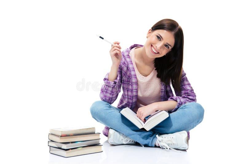 微笑的妇女坐与书的地板 免版税库存图片