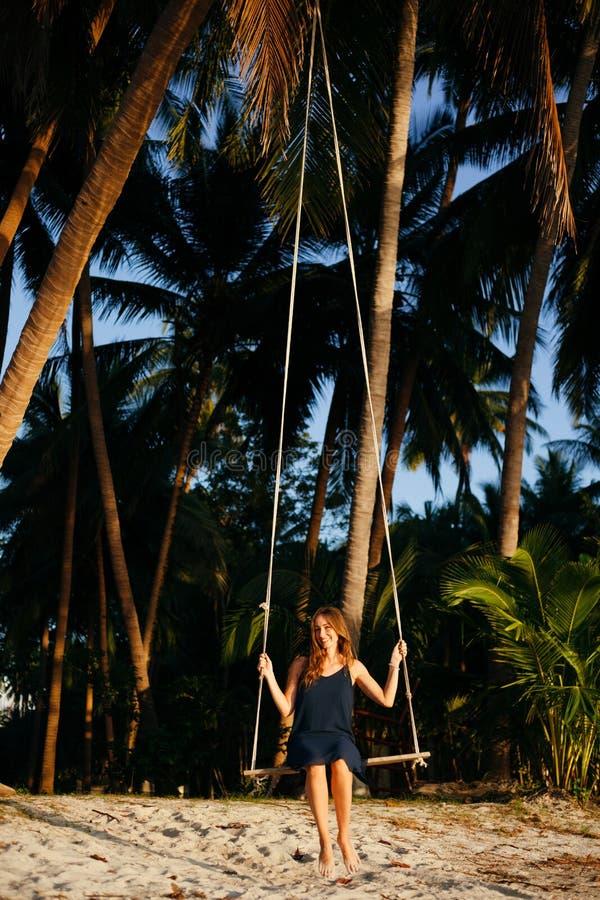 微笑的妇女坐在棕榈树之间的摇摆在海滩 库存图片