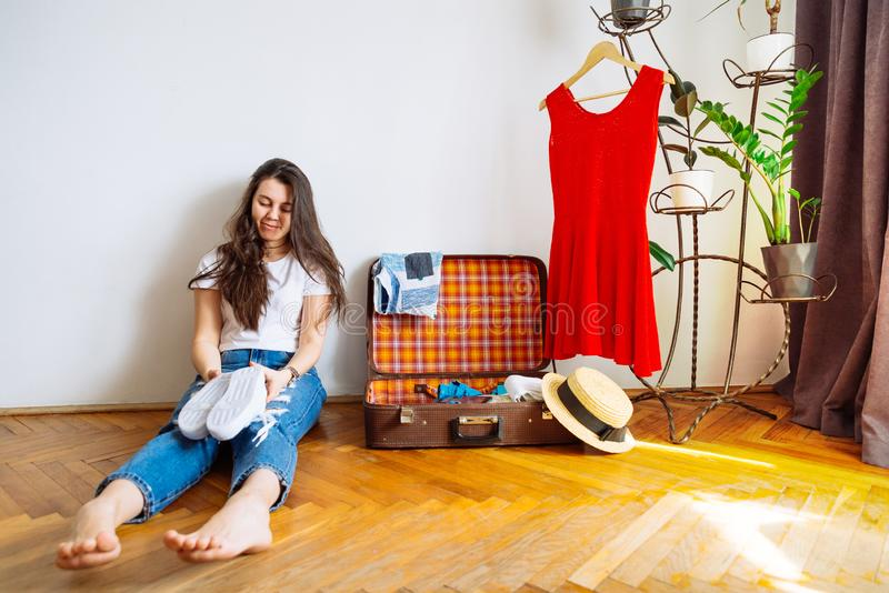 微笑的妇女坐地板在与衣裳的valise附近 包装bef 免版税库存照片