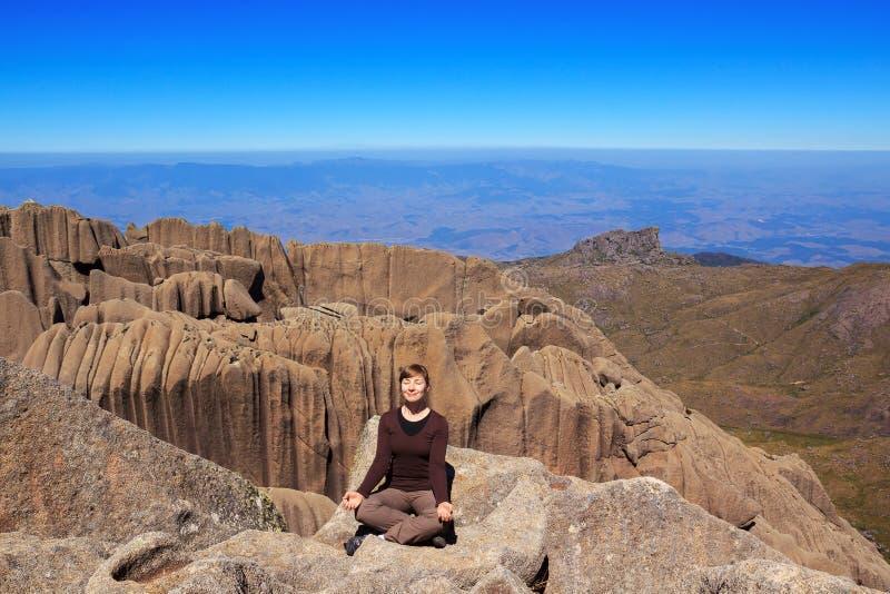 年轻微笑的妇女坐山瑜伽姿势的边缘 免版税库存照片