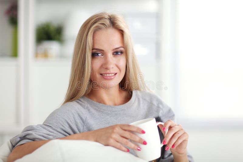 微笑的妇女坐有一个杯子的长沙发在她的手上和,她在她前面看 库存图片