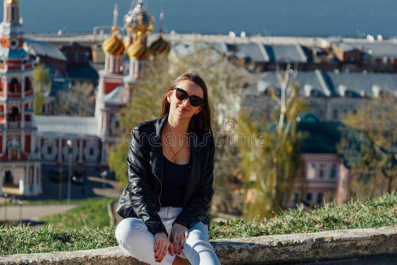 微笑的妇女坐栏杆由城市河 图库摄影