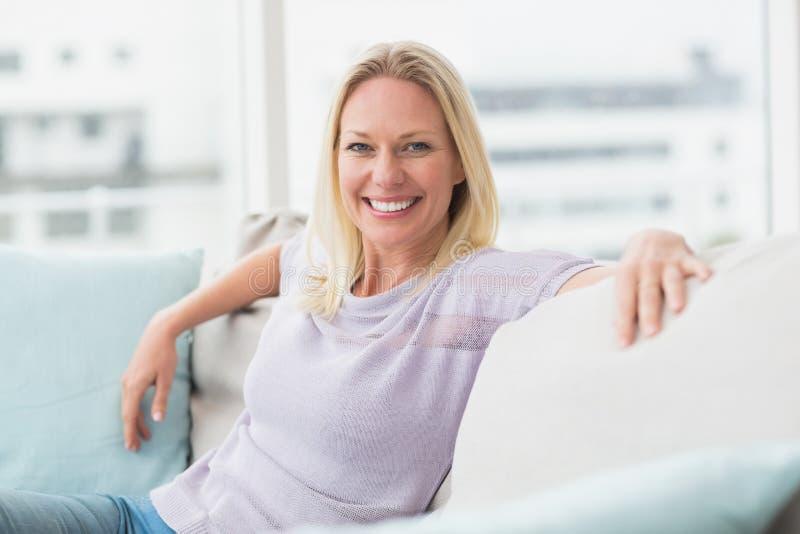 微笑的妇女坐沙发在客厅 库存照片