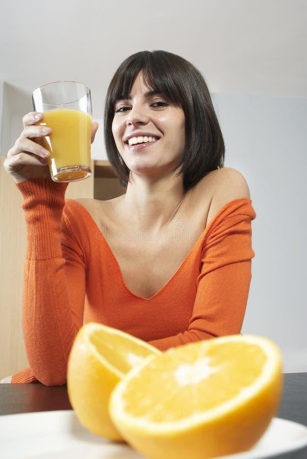 微笑的妇女对负玻璃用橙汁 库存照片