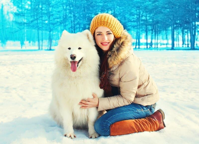 年轻微笑的妇女所有者与白色萨莫耶特人狗冬天 库存照片