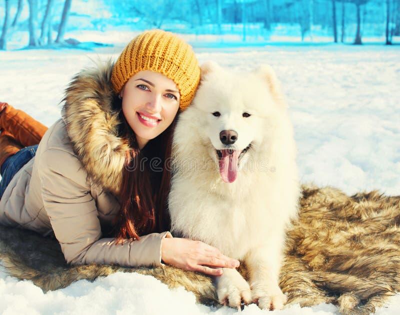 微笑的妇女所有者和白色萨莫耶特人尾随说谎在雪冬日 免版税库存照片
