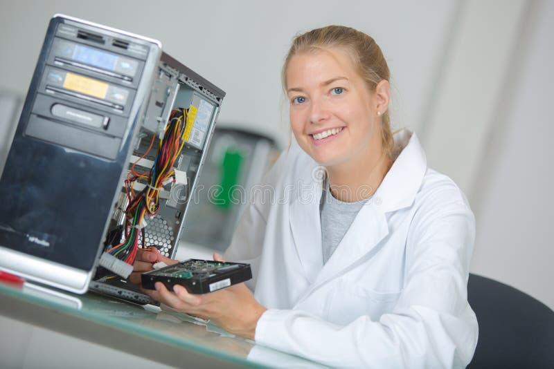 年轻微笑的妇女技术员修理计算机 免版税库存图片