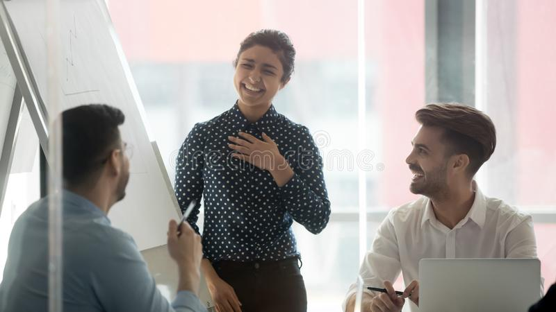 微笑的妇女报告人笑谈话与同事在简报 库存照片