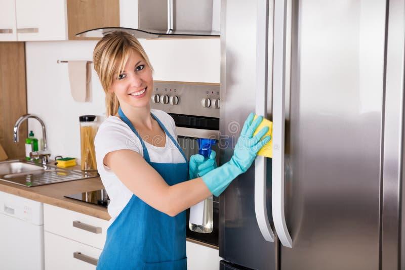 微笑的妇女清洁冰箱 库存照片