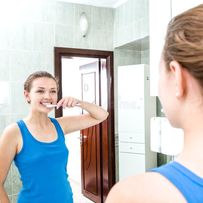 年轻微笑的妇女清洁牙 免版税库存图片