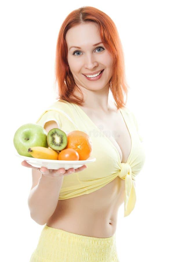 微笑的妇女用在牌照的果子 库存照片