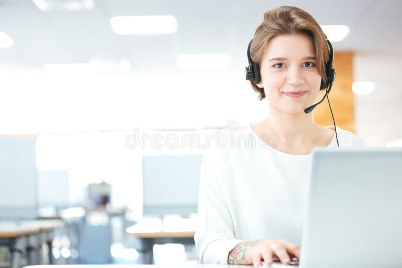 微笑的妇女用户支持在办公室告诉操作员 图库摄影