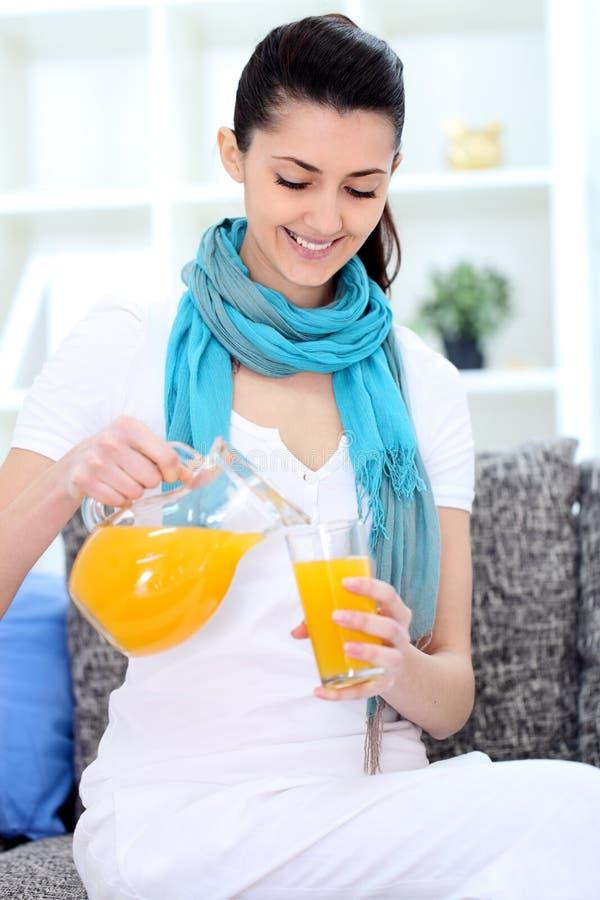 微笑的妇女用汁液 免版税库存照片