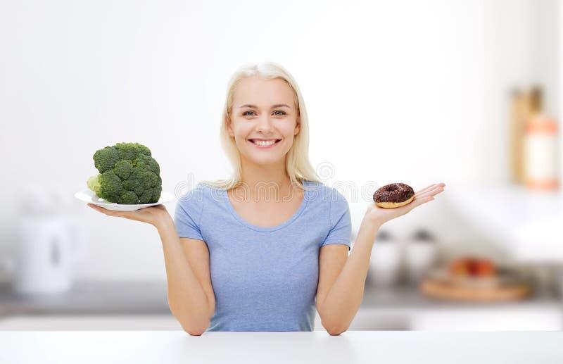微笑的妇女用硬花甘蓝和多福饼在厨房 库存图片