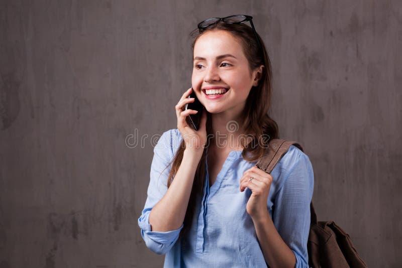 微笑的妇女画象戴眼镜的讲话由手机 免版税库存照片