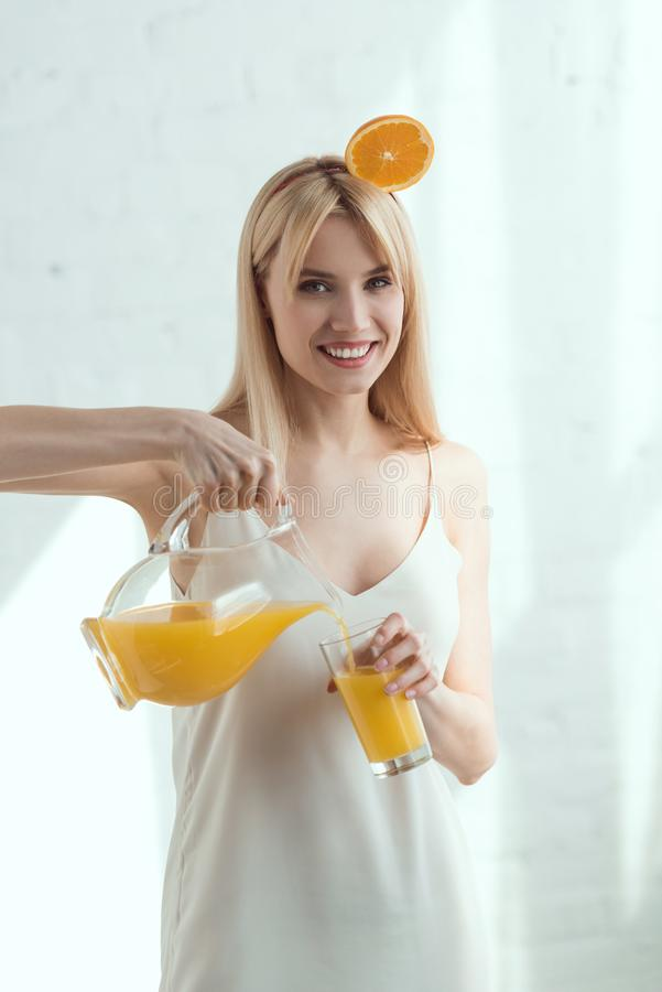 微笑的妇女画象有桔子片断的在头倾吐的汁液的到玻璃素食主义者里 库存图片