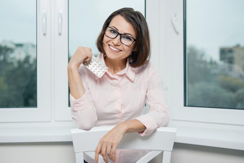 微笑的妇女画象有玻璃和轻的衬衣的有药片,女性藏品和显示药片的水泡的反对窗口 库存图片