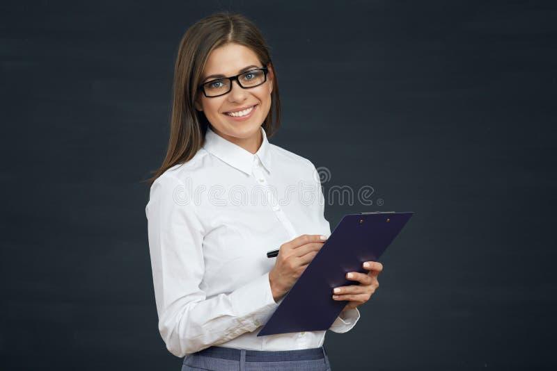 微笑的妇女社会雇员在剪贴板写 库存照片