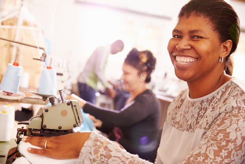 微笑的妇女缝合在社区车间的,南非 免版税库存图片