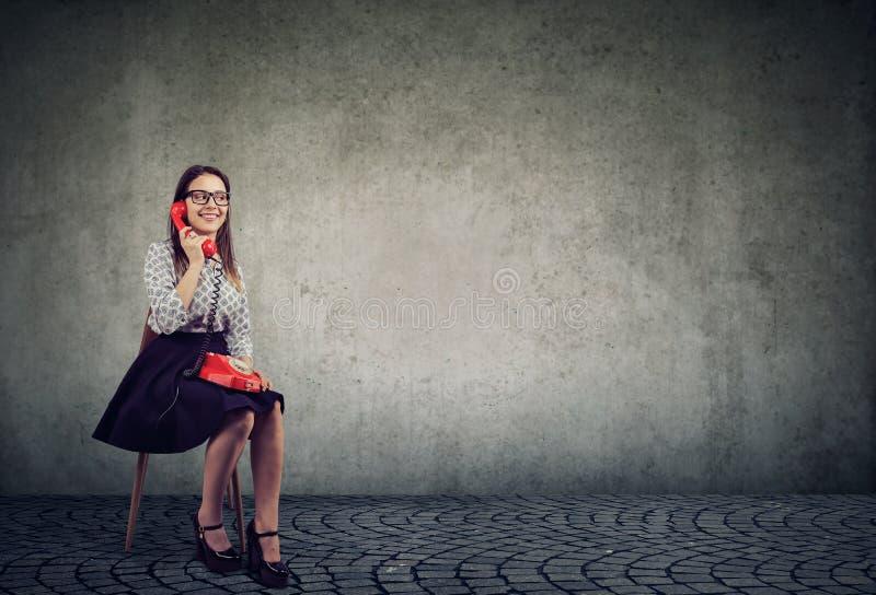 微笑的妇女说在电话里 免版税库存图片