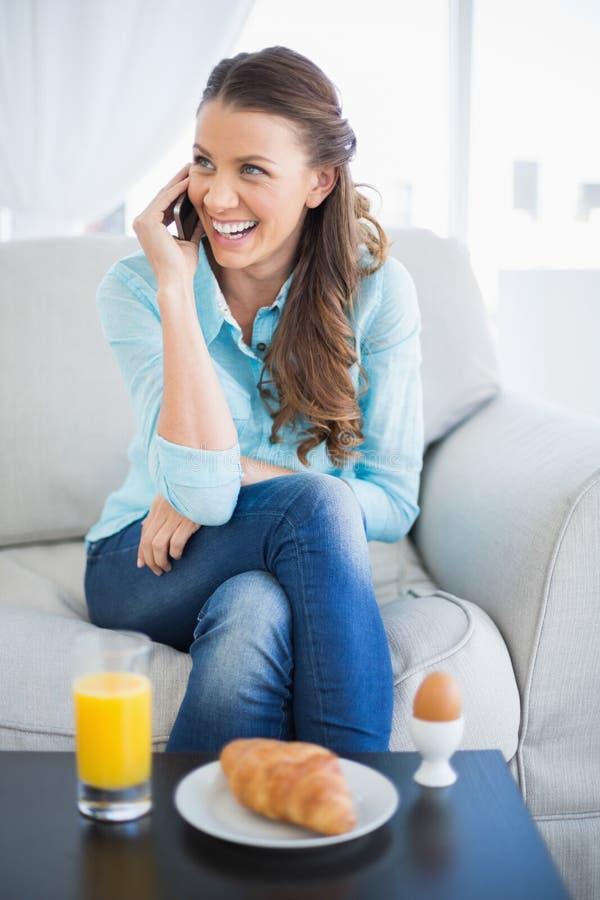 微笑的妇女谈话在电话坐沙发 免版税库存照片