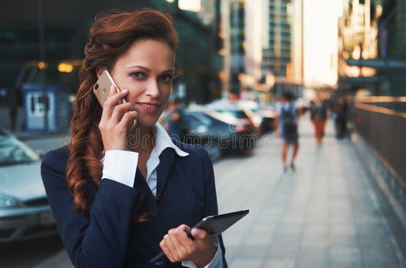 微笑的妇女谈话在街道上的手机 免版税库存图片