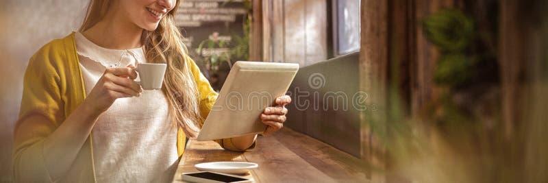 微笑的妇女饮用的咖啡和使用片剂 免版税库存照片