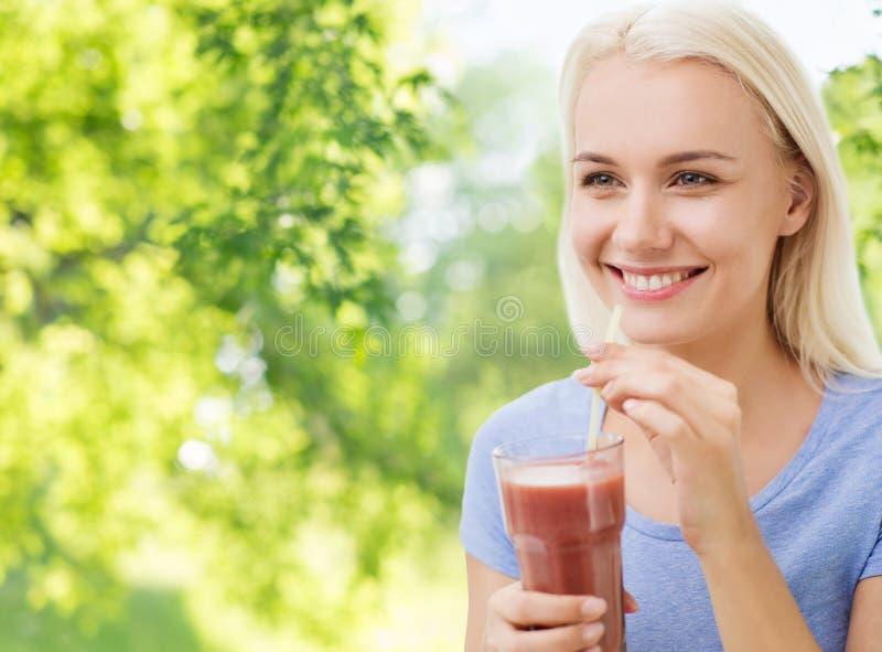 微笑的妇女饮用的汁液或震动 免版税图库摄影