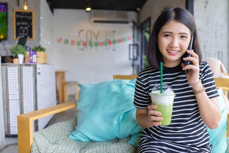 微笑的妇女饮用的matcha绿茶拿铁在咖啡馆的早晨 拿着在咖啡馆的亚裔女孩绿茶玻璃 免版税库存照片