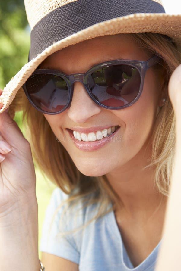 微笑的妇女首肩画象有太阳帽子的 免版税库存图片