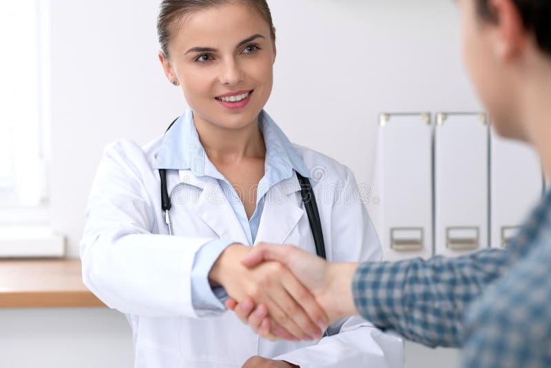 医治微笑的妇女,当与她的男性患者握手时 医学和信任概念 免版税库存图片