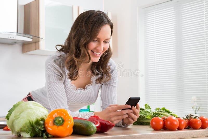 微笑的妇女,当使用手机时 免版税库存照片