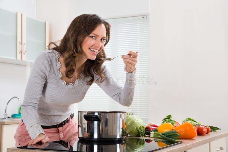 微笑的妇女,当品尝膳食在厨房里时 免版税库存照片