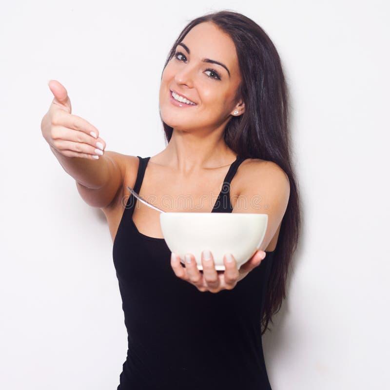 微笑的妇女,当拿着碗时。 库存照片