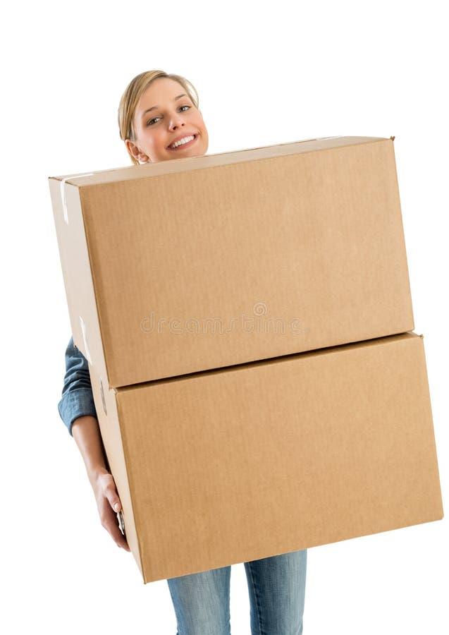 微笑的妇女,当运载被堆积的纸板箱时 免版税库存图片
