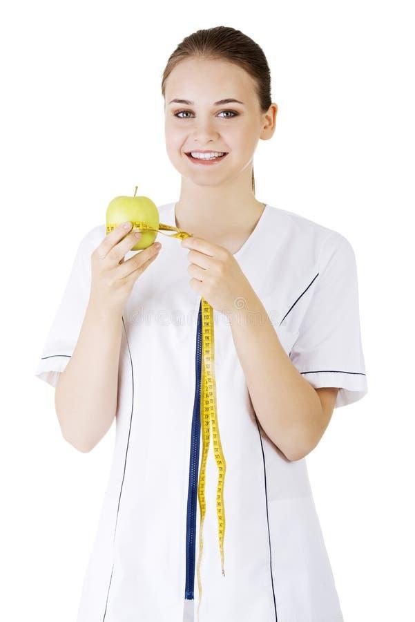 微笑的妇女医生用一卷绿色苹果和测量的磁带。 图库摄影