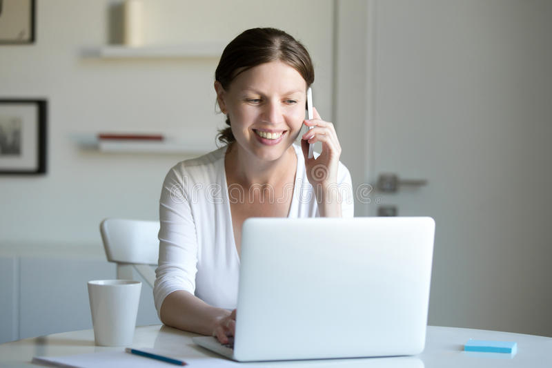 微笑的妇女画象在膝上型计算机附近的谈话在电话 库存图片