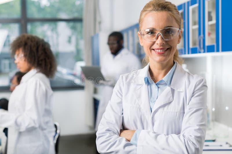 微笑的妇女画象白色外套和防护镜片的在现代实验室,在繁忙的女性科学家 免版税图库摄影