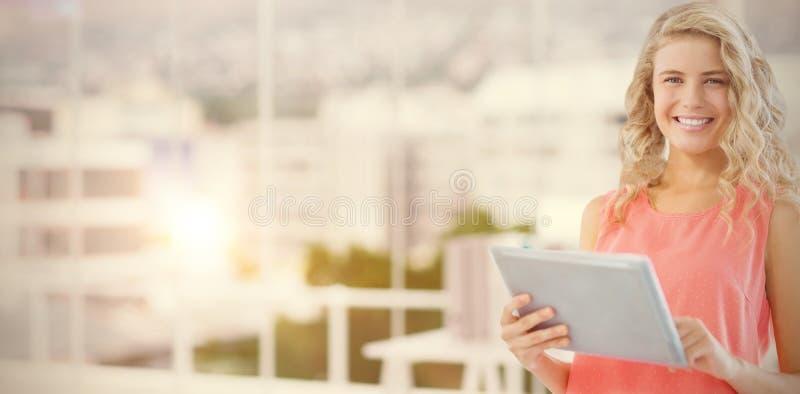 微笑的妇女画象的综合图象使用数字式片剂的在办公室 图库摄影