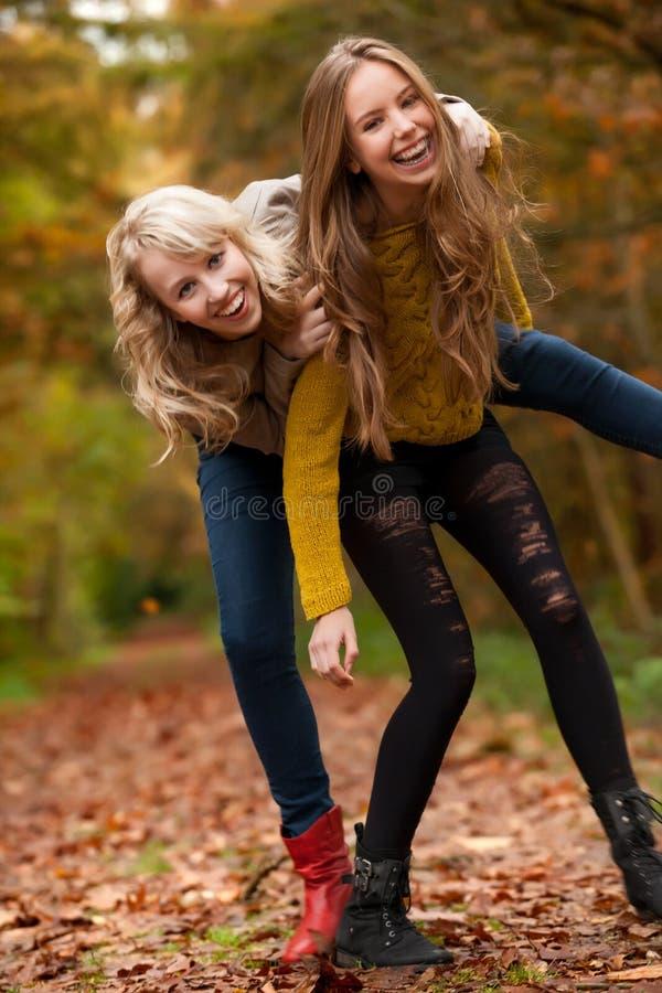 微笑的姐妹在森林里 免版税库存照片