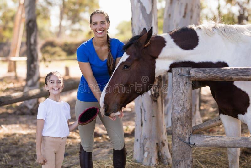 微笑的姐妹画象有马的 免版税库存照片