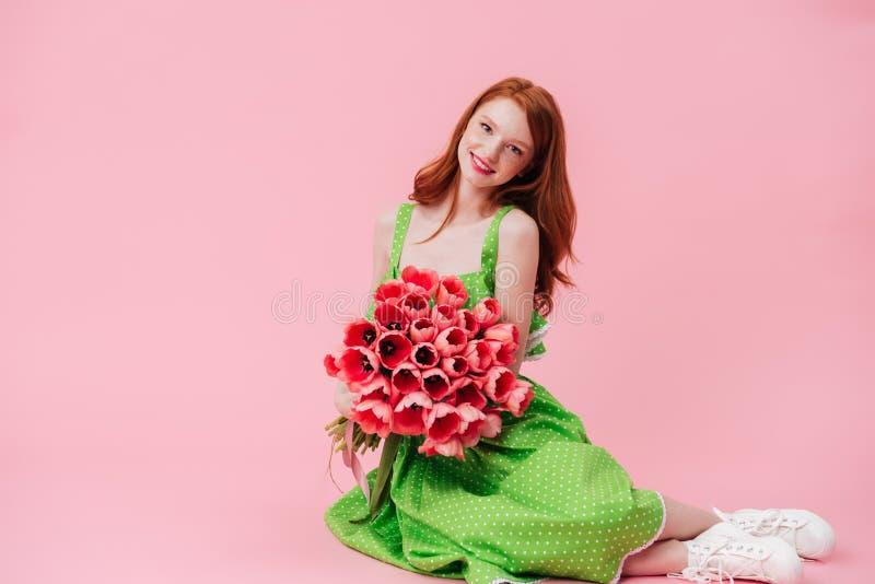 微笑的姜妇女坐与花花束的地板  免版税图库摄影