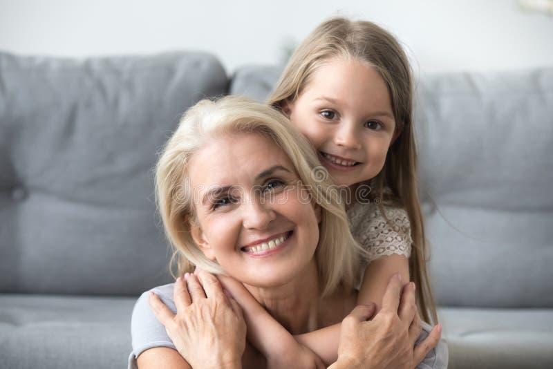 微笑的孙女肩扛祖母画象在家 免版税库存图片
