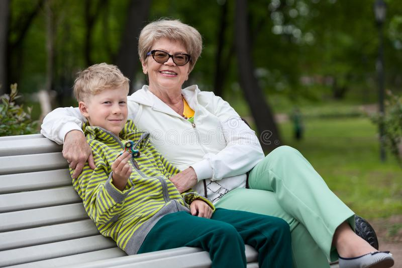 微笑的孙子使用与锭床工人小配件的,拥抱男孩,两个人的愉快的祖母 免版税库存照片