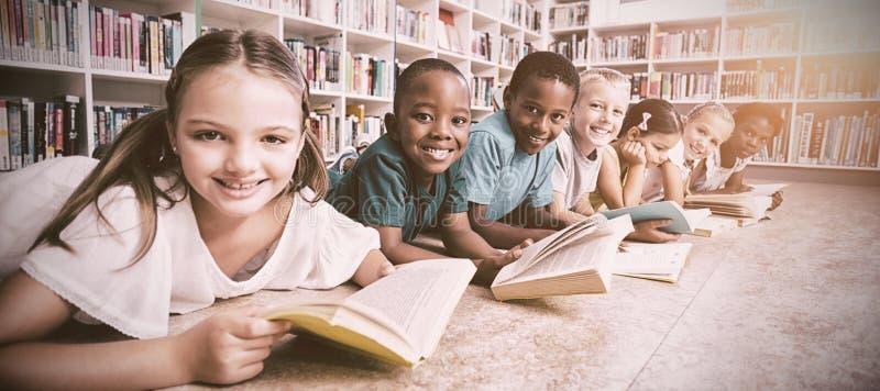 微笑的学校在图书馆里哄骗在地板阅读书 免版税库存照片