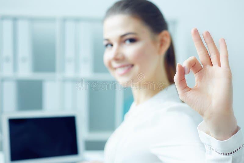 微笑的学生女孩满意对显示好姿态,坐的半轮的被完成的工作看在照相机,当工作时 免版税库存图片