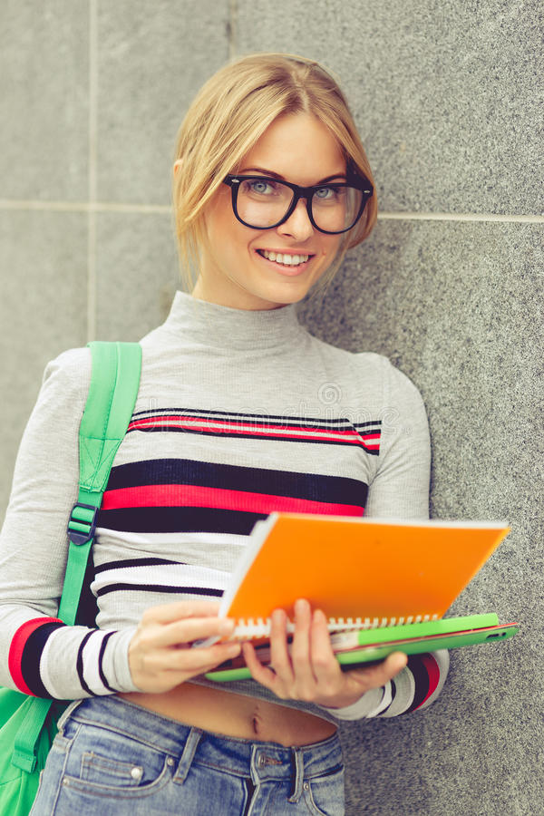 微笑的学生拿着在灰色墙壁上的笔记本 免版税图库摄影