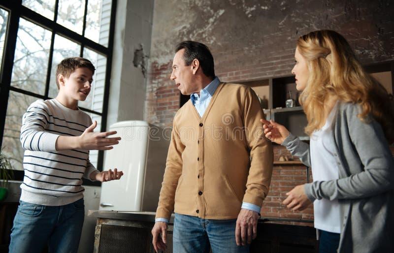 微笑的学生讲话与他的父母 免版税库存照片
